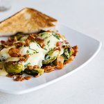 English Breakfast with roasted Brussel Sprouts, Hardwood-Smoked Bacon, Poached Eggs, and our Morning Story Hollandaise.