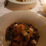 Op de voorgrond de vegetarische ravioli met daarachter de risotto met ossobuco