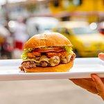 """Sabores colombianos concentrados en esta hamburguesa que le dará """"Envidia"""" a la competencia. Tajadas de longaniza sobre un queso Paipa derretido encima de una carne jugosa y nuestro pan de papa."""
