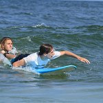 Reider on a surf lesson sending a student in to pop up!