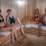 """The new pearl in our sauna area is """"Ritual Infusion Experience; hot air drift  and snow"""" at 160°F, 15–60% humidity.  The interior walls and seating steps around the infusion stove are made of brown Cedar  wood. The architecture creates a unique atmosphere and provides the scope for lighting effects in keeping with the infusions."""