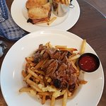 Smoked meat sandwich and poutine with smoked meat.