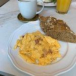 El chocolate caliente con huevos revueltos, pan de semillas y mantequilla, y el sandwich con zum