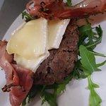 Hamburger di anatra su un letto di rucola con speck croccante e brie