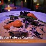 Raviollis con Tinte de Calamar Rellenos de camarón y crema bañados en salsa huancaina.