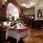 Particolare della sala con banco bar, cassa, accesso alle cucine e tavolo da norcino