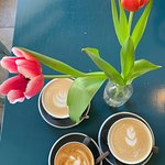 One flat white and two lattes accompanied by some beautiful tulips.