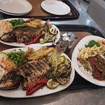 Greek specialties and fresh fish on grill.