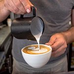 haciendo latte art en el curso de café y Barismo