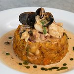 """""""La Pesca""""  Mashed plantain, cassava and sweet plantain base, shrimps, fish, octopus, mussels and calamari in a creole sauce."""