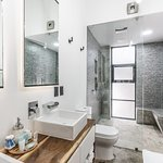 Loft 202 & 302 feature luxury showers with two rain shower heads, concrete bench and a double sink.