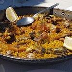 Paella de conejo, alcachofas y caracoles.