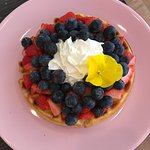 Strawberries, whipped cream and blueberries waffle