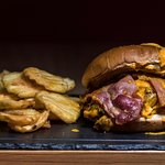 Bacon mushroom melt burger with cheddar sauce on the top. Burger 50% pork- 50% veal , bacon, mushrooms and cheddar sauce.