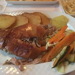 Sucking pig with apple sauce, roast potatoes and vegetables