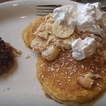 Banana Pudding topping on sweet potato pancakes with a side of sausage.