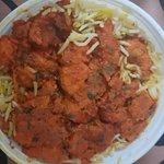 Boneless chicken curry on top of the biryani