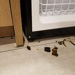 Broken glass on the floor in the kitchenette area by the refrigerator that had not been cleaned up.