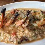Grilled Shrimp on a bed of BLT risotto bacon, tomato, basil, with a tomato-basil glaze.