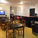 Petite salle de restaurant avec télévision. Une autre salle plus grande permet d'accueillir en t