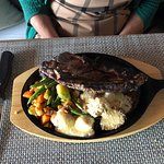 Charcoal grilled ribeye steak that came out still sizzling on the cast iron platter.