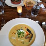 Sweet corn and crab soup, with mussels, scallops and shrimp, served with creme fraiche and chili