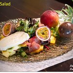 Variety of fresh leaves with goat cheese, Greek prosciutto, and seasonal fruits