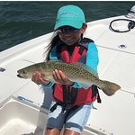 Kids love fishing! Here's one of our young anglers holding a beautiful sea trout that she caught and released on today's inshore charter.