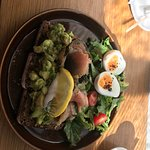 Avocado on dark rye toast with salmon gravadlax and seasoned soft boiled egg
