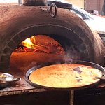 The huge pan goes into the wood-fired oven