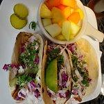 pulled pork tacos with fresh fruit side.