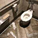 Trash overflows and toilet paper litters the floor of the women's bathroom.