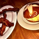 The Daily - scramble egg and cheese in a pretzel roll with a side of bacon.