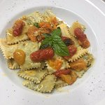 Homemade Ravioli filled with spinach and ricotta cheese flavored cherry tomatoes and basil