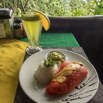 Red bell pepper stuffed with cheese and chopped veggies, rice and guacamole on side; lemonade with herba buena (mint relative)