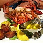 Baked Stuffed Lobster with seafood stuffing and with summer vegetables and roasted potatoes.