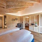 Panorama Suite mit Balkon zum Silsersee. Zwei separate Badezimmer mit Dusche und Badewanne, DuschWC, Wohnraum und separatem Schlafzimmer, alles in Arvenholz