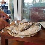 zeebaars in zoutkorst wordt aan de tafel schoongemaakt en geserveerd.