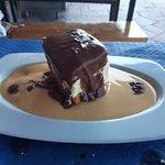 Bizcocho con helado recubierto de chocolate caliente, en un lecho de natillas.