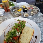 Oysters and Burrata salad. Peach salad in background.