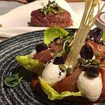 Entrantes, en salada de tomates y al fondo un steak tartar.