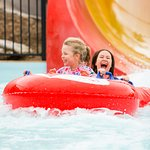 Two young kids on a water slide