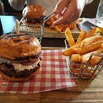 Shredded beef in a bun on a stupid wooden board with chips in a stupid chip basket. Beef over po