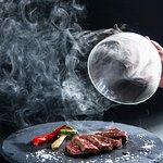 料理の仕上げに僅かな時間、煙で燻製の香りをつける調理法。焼き上げたお肉を煙で覆い、お客様の目の前で煙を逃してから ご提供いたします。