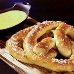 Queso Dip and Pretzels Two soft baked pretzels with queso dip.