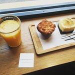 Desayuno de zumo de naranja natural con cheese cake delicioso y kouign amman.