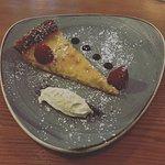 Homemade lemon tart with clotted cream and raspberries.