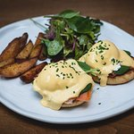 SALMON BENEDICT with Smoked Salmon, Hollandaise Sauce and Salad.