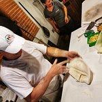 Chef Marcello abrindo a massa para preparar a pizza