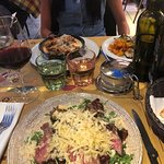 Steak with rocket salad and cheese (near). Lasagne (far)